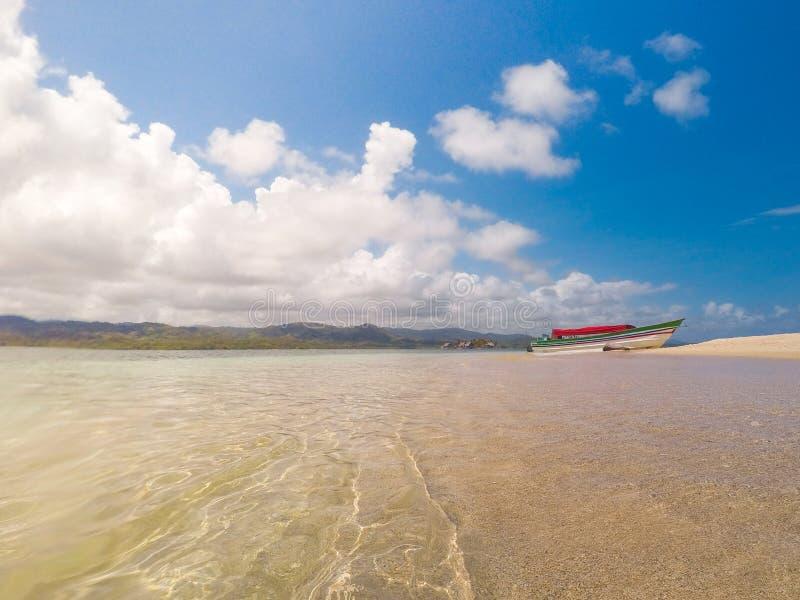 Вода океана и крупный план песка на пляже с шлюпкой в предпосылке - стоковое фото