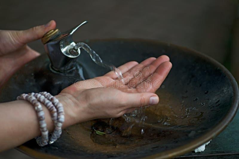 Вода от выпивая фонтана пропускает в руку ` s женщины стоковое изображение