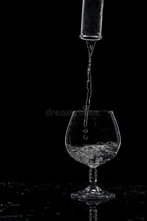 Вода полита в прозрачное стекло от бутылки на темной предпосылке стоковое фото