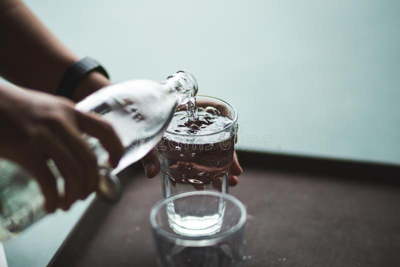 Вода руки лить в стеклянную бутылку стоковое изображение rf