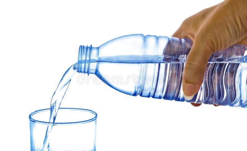 Вода руки ` s женщин лить от пластичной бутылки в стекло  стоковое фото