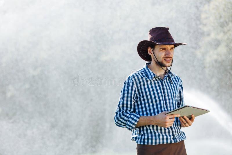 Вода системы опылительного орошения шляпы технологии плантации планшета проверки работника солнца agronomist человека фермера циф стоковое фото rf