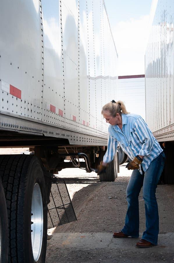 Водитель грузовика женщины поднимая посадочное устройство на трейлере стоковое фото