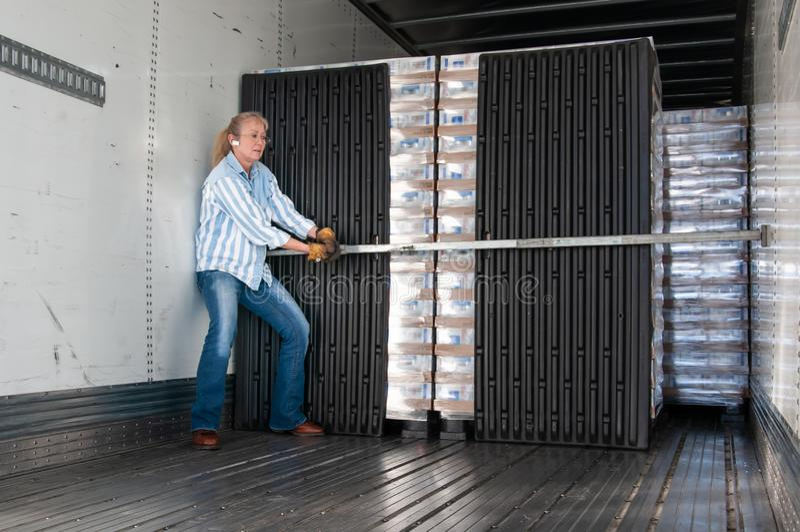 Водитель грузовика женщины устанавливая ее замки нагрузки стоковое фото rf