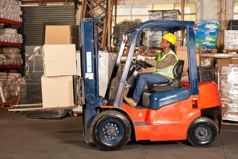 Водитель грузоподъемника транспортирует груз в складе стоковые изображения