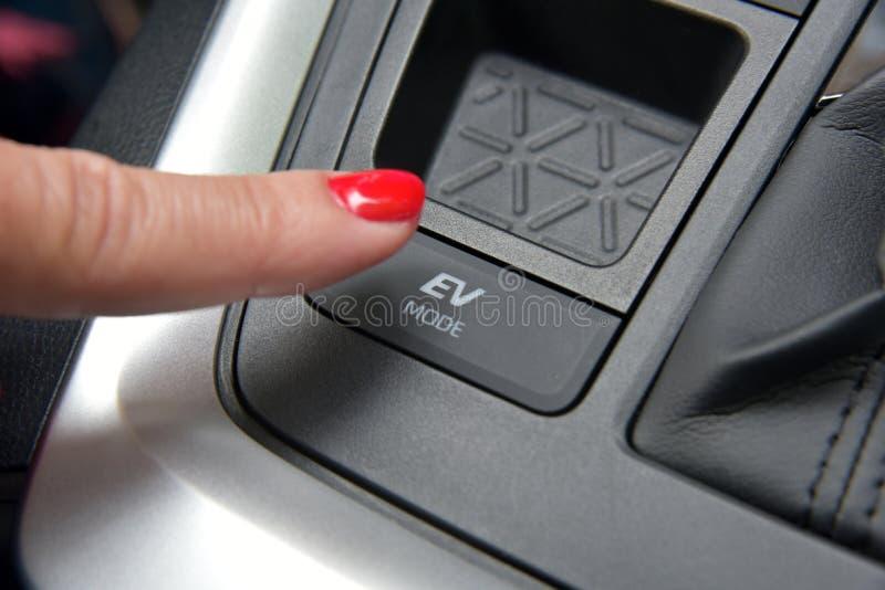 Водитель-женщина активирует электрический режим вождения в гибридном автомобиле стоковое изображение rf