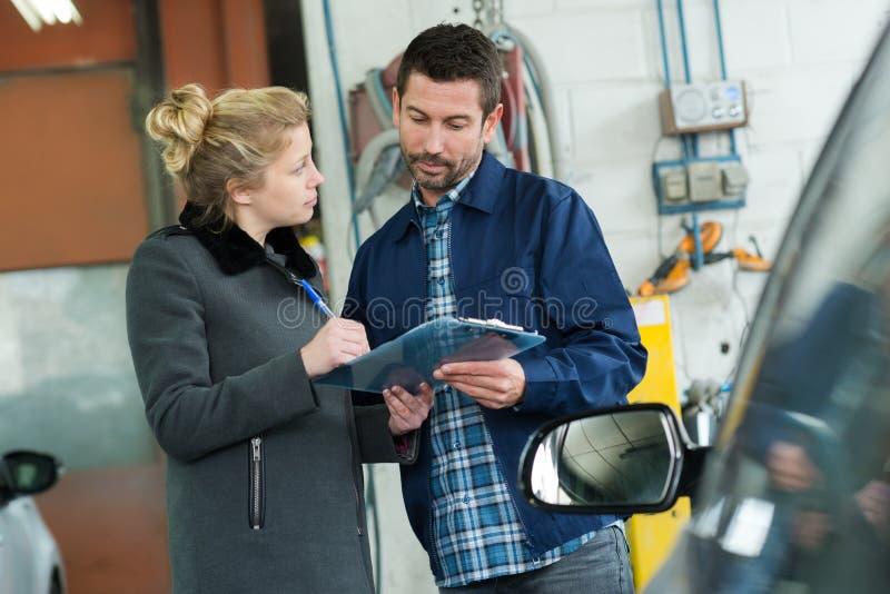 Водитель женщины говоря со страховым инспектором стоковые фото