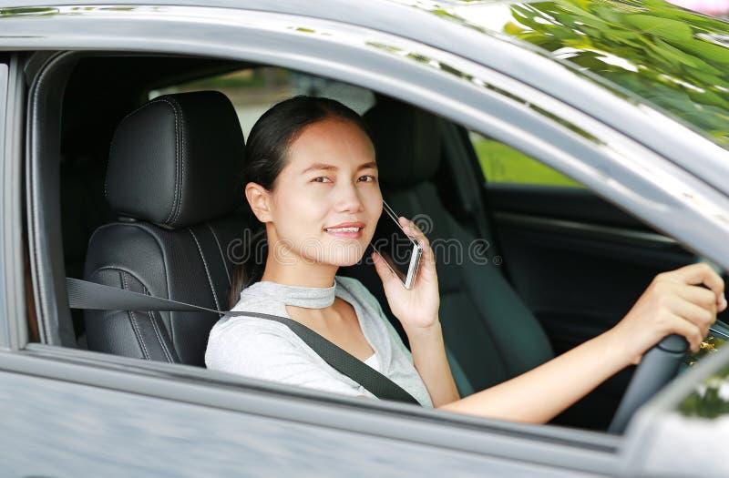 Водитель женщины используя ее мобильный телефон пока управляющ автомобилем стоковая фотография