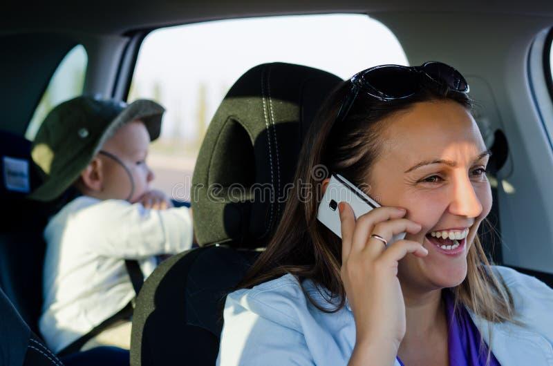Водитель женщины смеясь над на ее черни стоковые фото