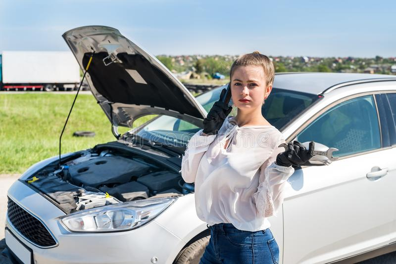 Водитель женщины с гаечными ключами вызывая для помощи стоковые изображения rf