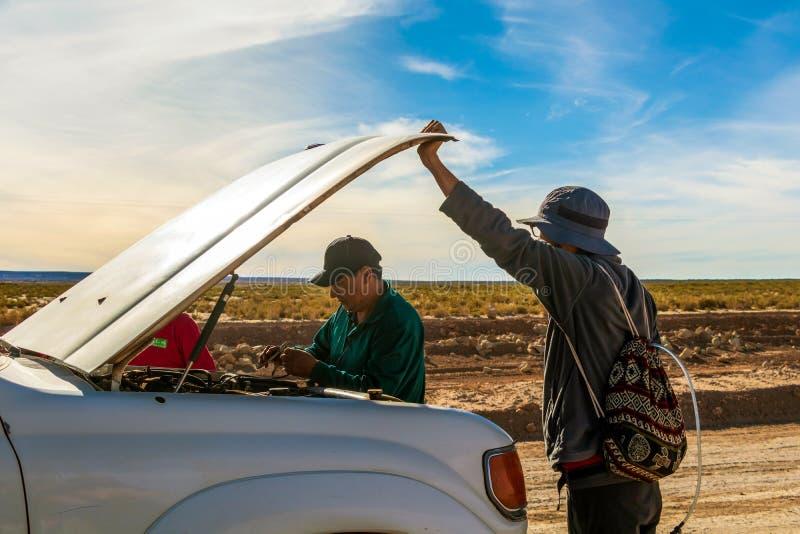 Водитель и туристы фиксируют сломленный автомобиль во время путешествия виллиса 4x4 на боливийце Altiplano, Боливии стоковые фотографии rf