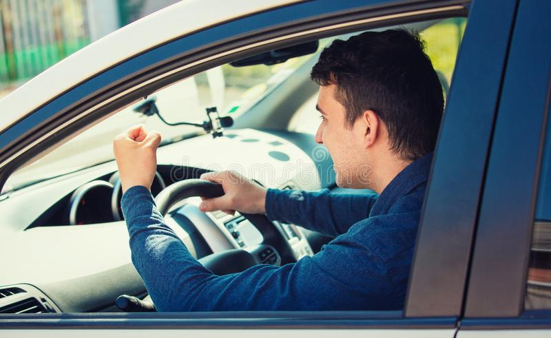 Водитель молодого человека выкрикивая и тряся его кулак угрожает другой автомобилистки стоковая фотография