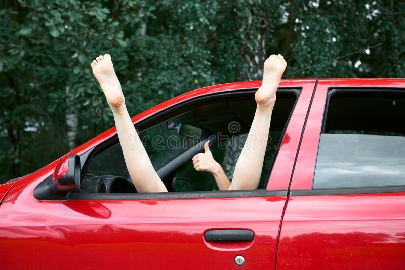 Водитель молодой женщины отдыхая в красном автомобиле, положил ее ноги на окно и показывать автомобиля, счастливая концепция пере стоковые фотографии rf