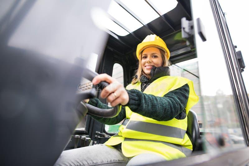 Водитель платформы грузоподъемника женщины в промышленной зоне стоковые фото