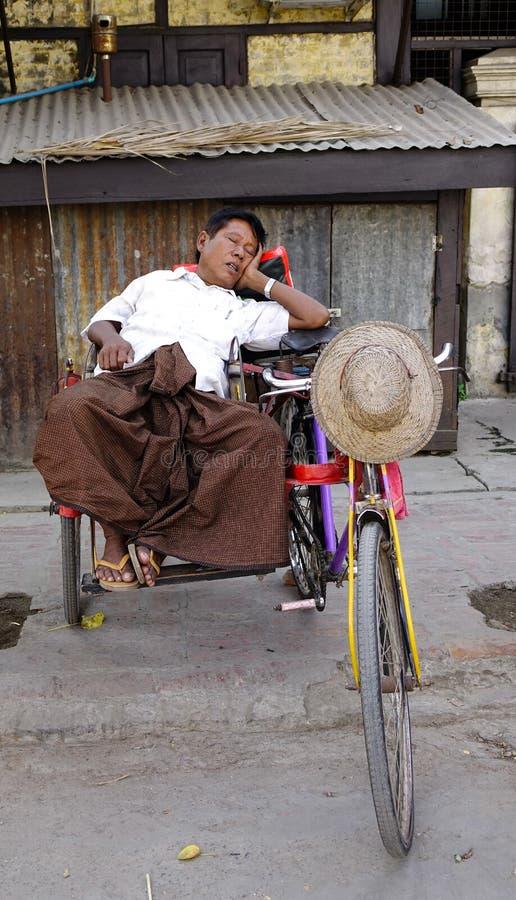 Водитель рикши спит на его велосипеде стоковые изображения rf