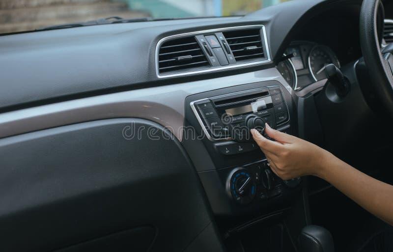 Водитель руки касаясь экрану и поворачивая дальше систему автомобильного радиоприемника, кнопку на приборной панели в панели авто стоковая фотография rf