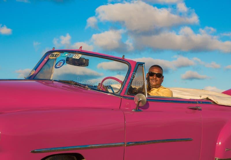 Водитель сидит в классическом американском розовом Chevy стоковое фото