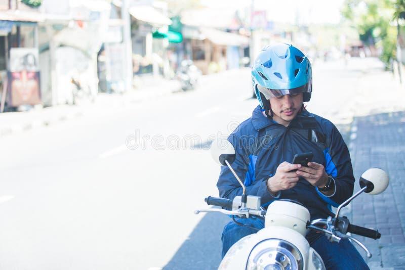 Водитель такси мотоцикла отправляя СМС на мобильном телефоне на стороне  стоковое фото rf