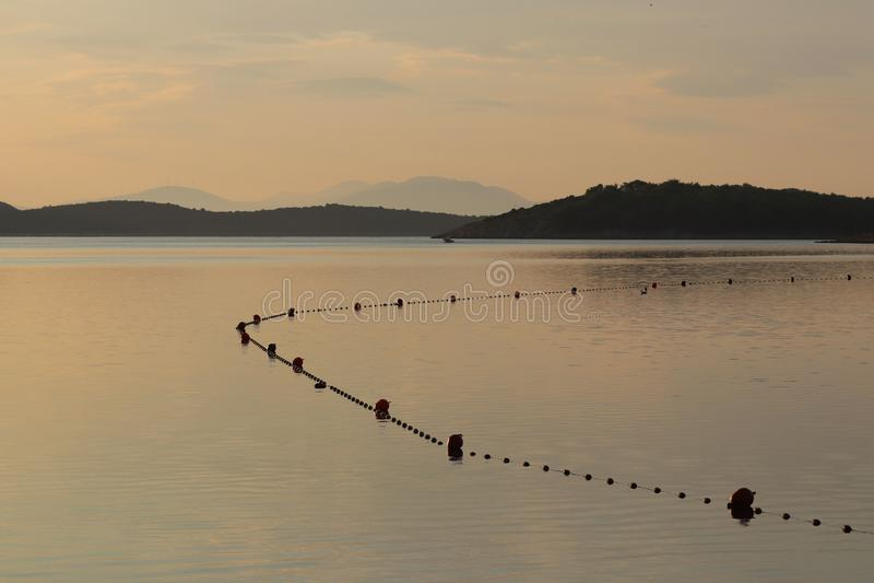 Водное пространство моря запланировано для купать отдыхающих ограженные с томбуями для безопасности Остатки на воде в раннем утре стоковое изображение rf