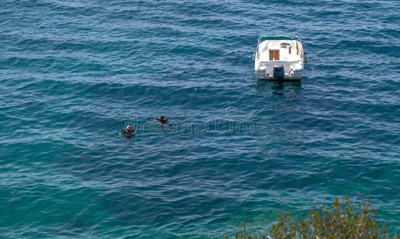 2 водолаза акваланга ныряют на поверхности моря около их шлюпок стоковое фото
