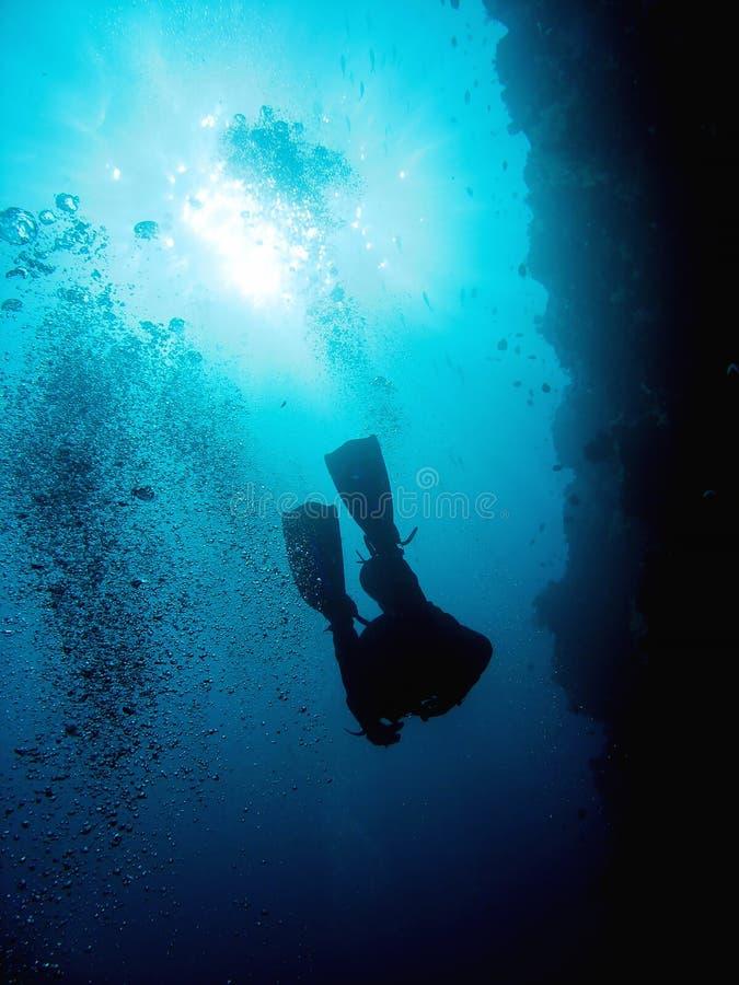Водолаз акваланга получает в глубокую пещеру Фото в сизоватом тоне с солнечным светом в воде стоковая фотография rf
