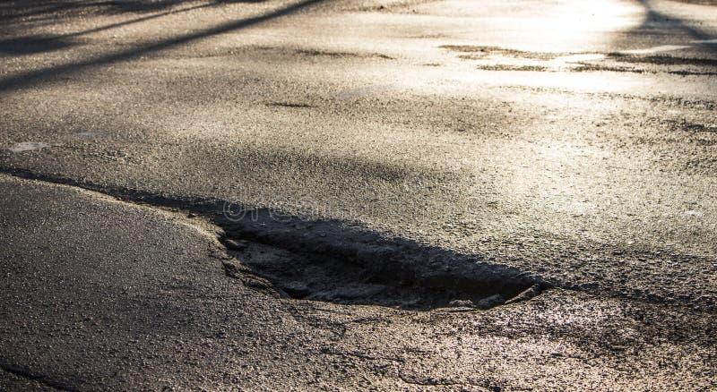 Водоналивная рытвина на заасфальтированной дороге стоковое изображение rf