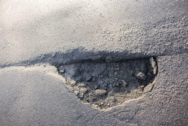Водоналивная рытвина на заасфальтированной дороге стоковое фото rf