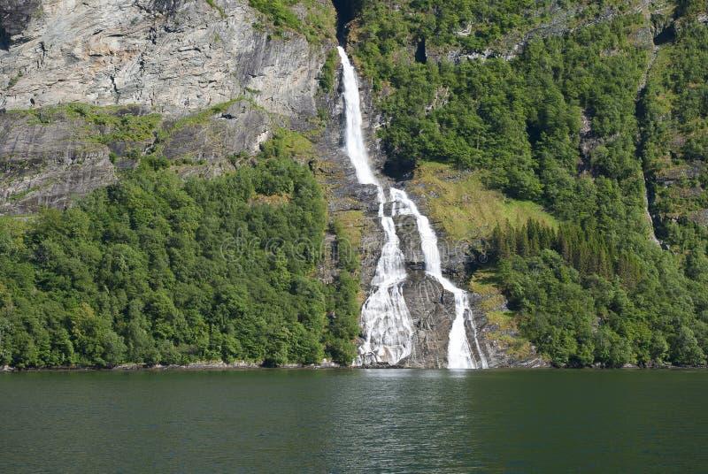 Водопад от зеленого холма в Норвегии стоковые изображения