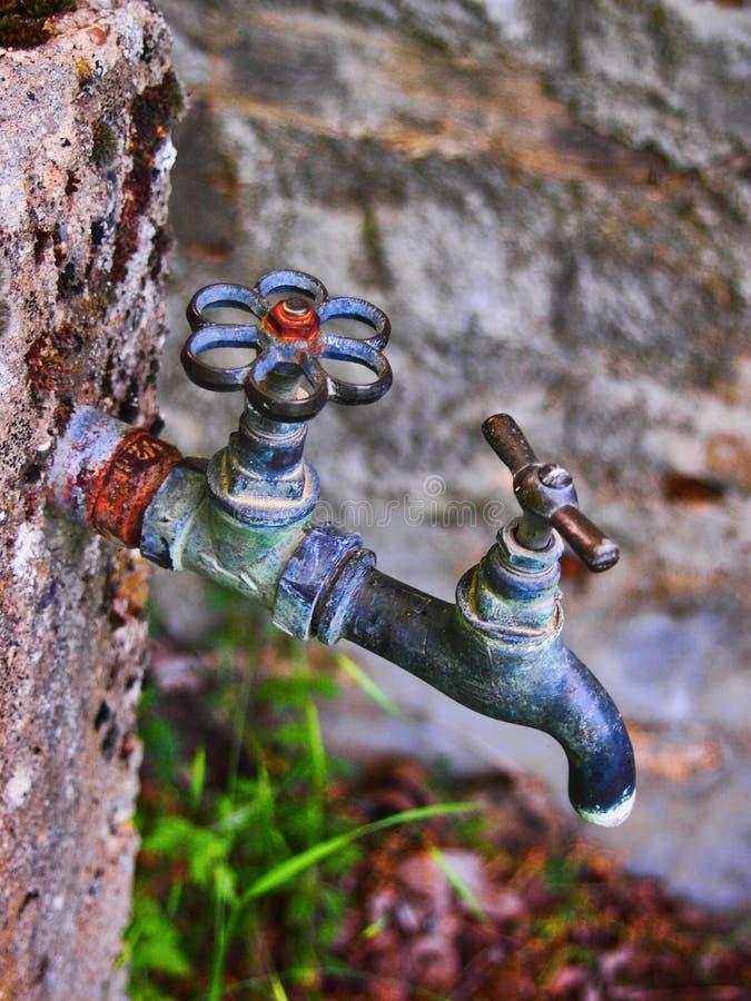 Водопроводные краны старого стиля вне греческого дома в деревне стоковые изображения