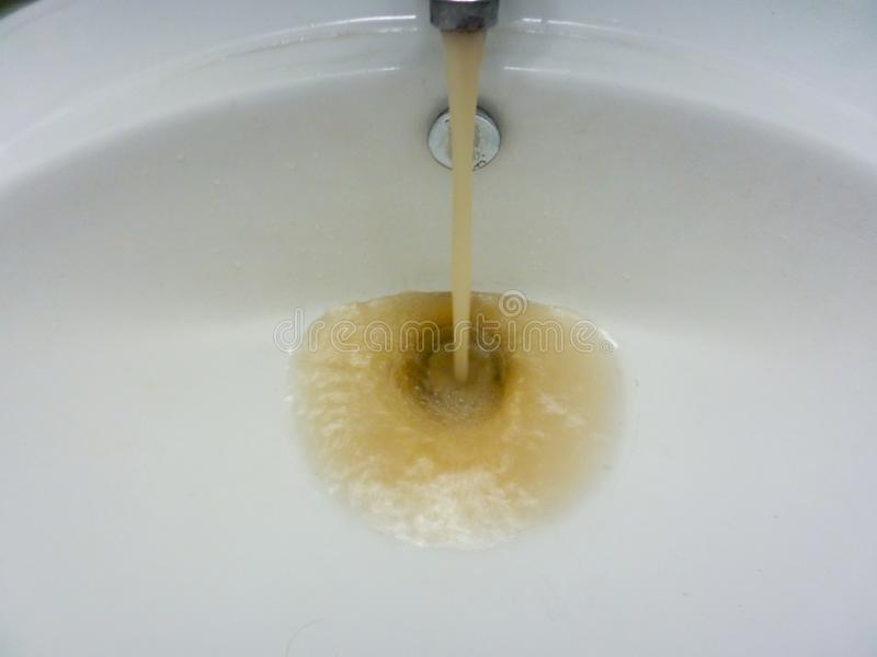 Водопроводный кран с бежать пакостная тинная вода в раковине стоковые фото