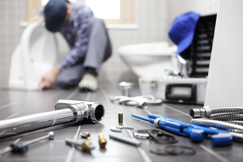 Водопроводчик на работе в ванной комнате, паяя ремонтные услуги, собирает стоковая фотография