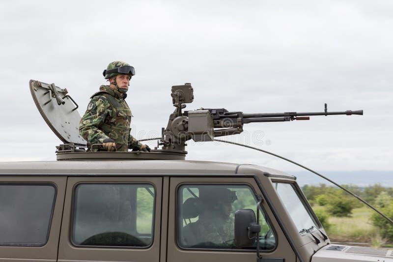 Военное транспортное средство с крупнокалиберным пулеметом и солдатом стоковые фото