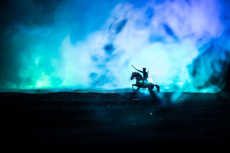 Военнослужащий (или воин) на лошади с мечом, готовым к бою, и солдаты на темном туманном фоне Битва стоковые фотографии rf