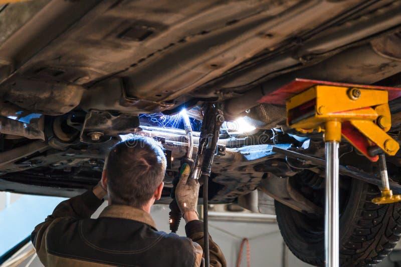 Военнослужащий сваривает звукоглушитель на автомобиле заваркой аргона стоковое изображение