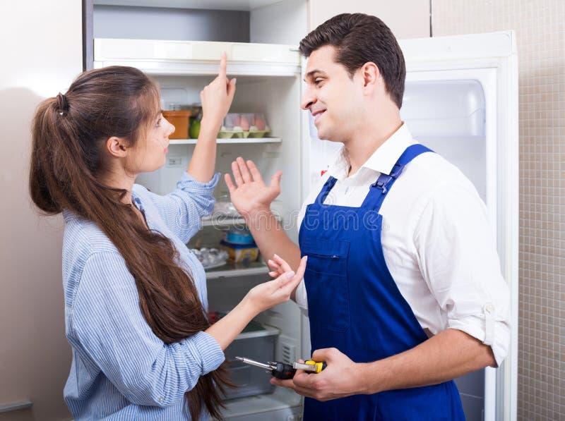 Военнослужащий спрашивая домохозяйке технических проблем с холодильником стоковые изображения rf