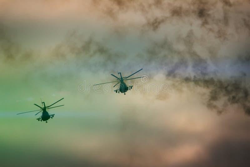 Военный вертолет увольнял ракеты анти--панцыря на заходе солнца стоковая фотография