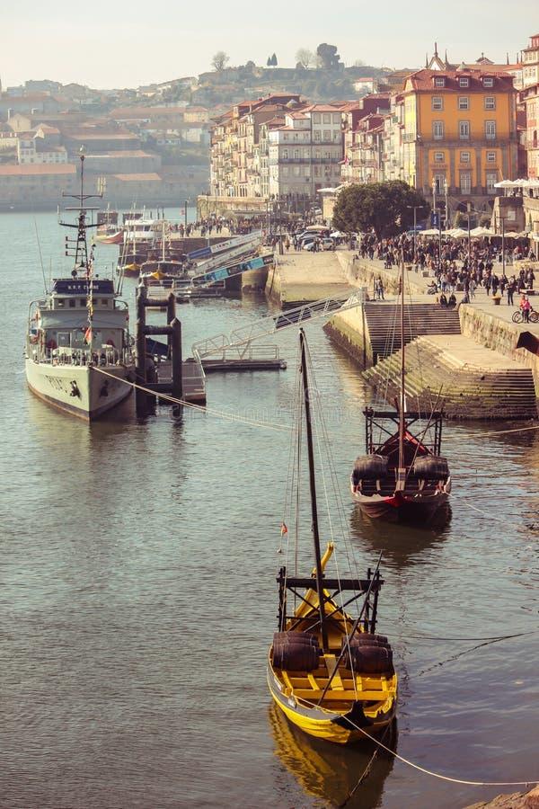 Военный корабль и традиционные деревянные шлюпки rabelo с бочонками вина на реке Дуэро в Порту, Португалии стоковое фото rf