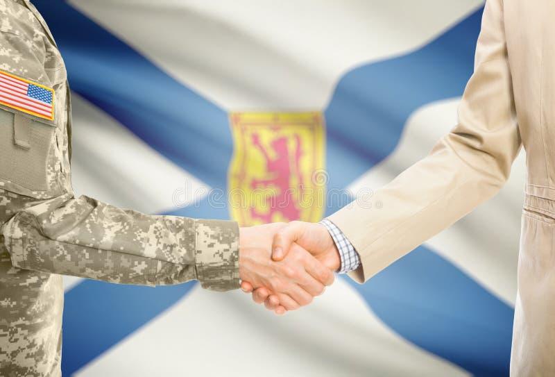Военный США в равномерном и гражданском человеке в костюме тряся руки с некоторым флагом канадской провинции на предпосылке - Нов стоковые фотографии rf