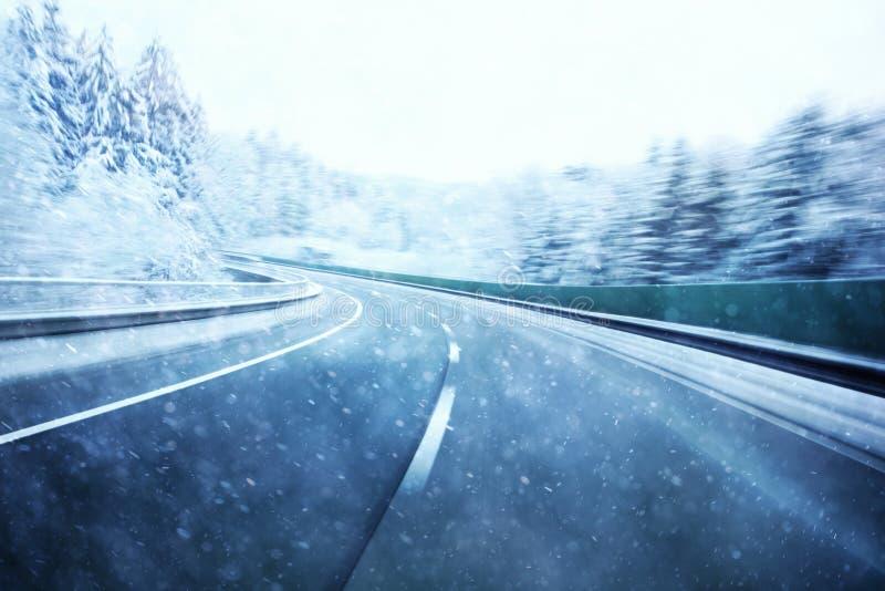 Вождение автомобиля запачканное конспектом быстрое на снежном шоссе стоковое фото