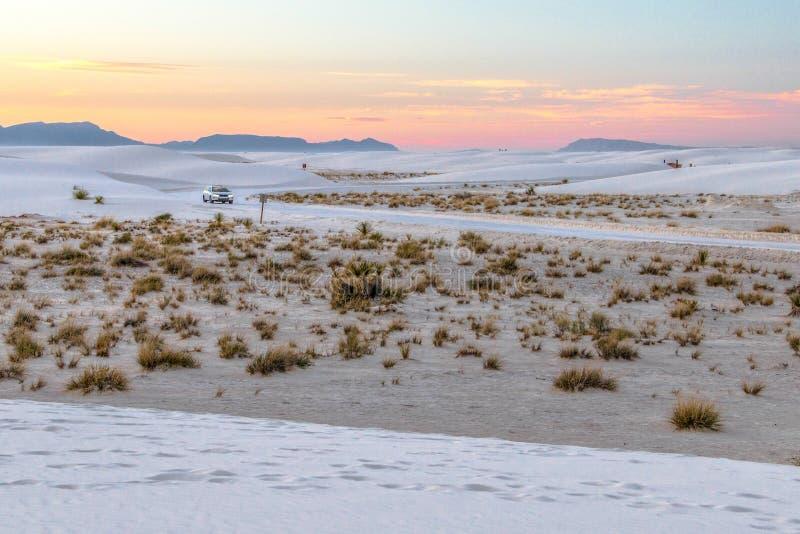 Вождение автомобиля на удаленной дороге захода солнца пустыни стоковое изображение