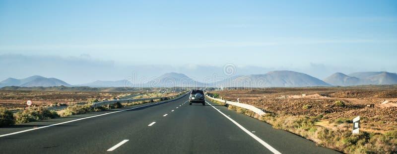 Вождение автомобиля прочь к горам в пустыне Канарских островов стоковая фотография rf