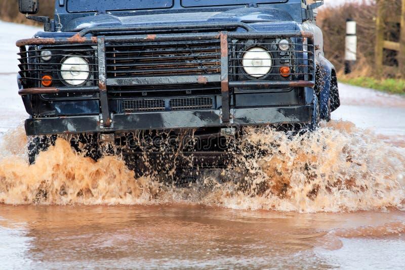 Вождение автомобиля через нагнетаемую в пласт воду на дороге стоковое изображение
