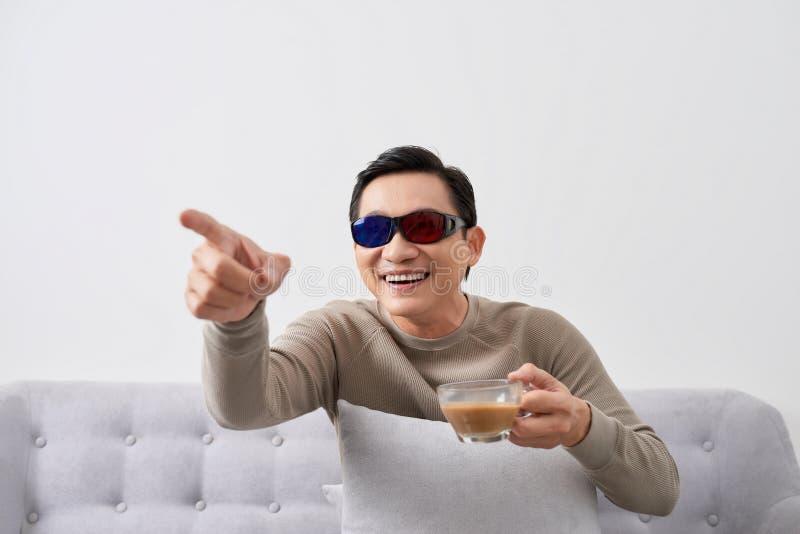 Возбуждая ЖК-ТЕЛЕВИЗОР дозора молодого человека трехмерный со стеклом глаза в живущей комнате стоковое фото rf