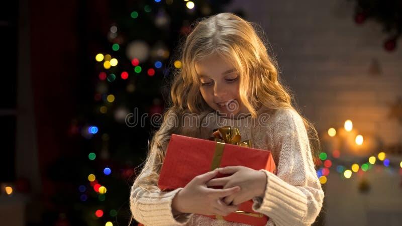 Возбужденная белокурая девушка держа длиной ожидала присутствующей, волшебной атмосферы рождества стоковые фотографии rf