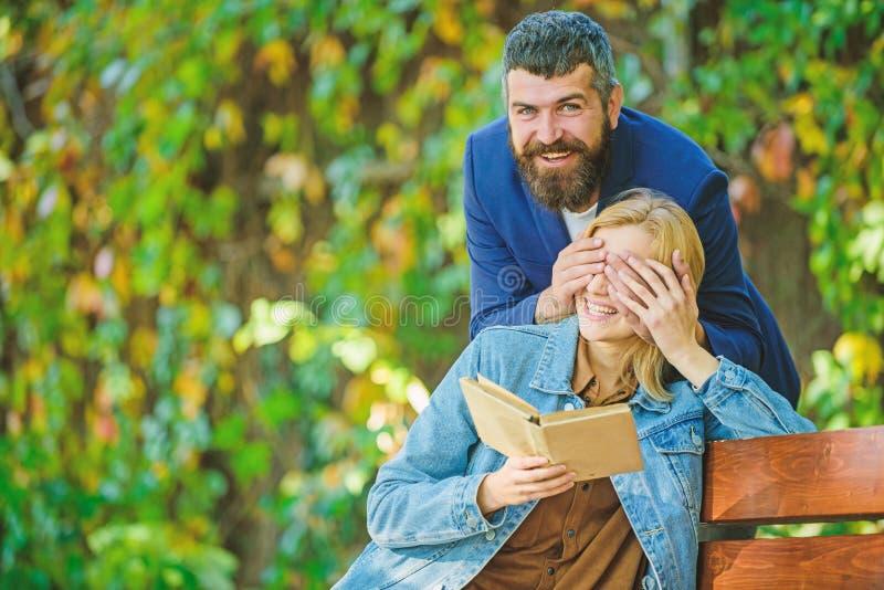 Возбужденная девушка пробуя угадать кто стоит за ей парень покрывая ее глаза руками и усмехаться шаловливая весна стоковое фото