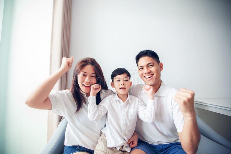 Возбужденная и счастливая семья с поднятыми оружиями пока смотрящ телевидение дома стоковая фотография