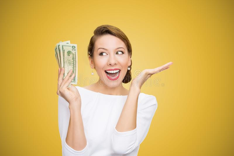 Возбужденная куча удерживания женщины долларов выглядя супер счастливым на яркой желтой предпосылке стоковая фотография
