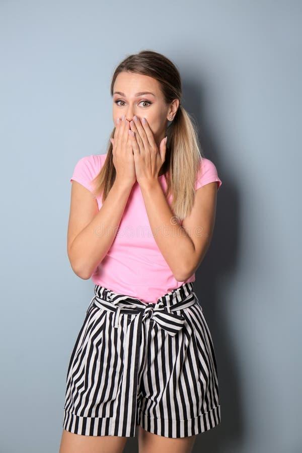 Возбужденная молодая женщина на предпосылке цвета стоковые фотографии rf
