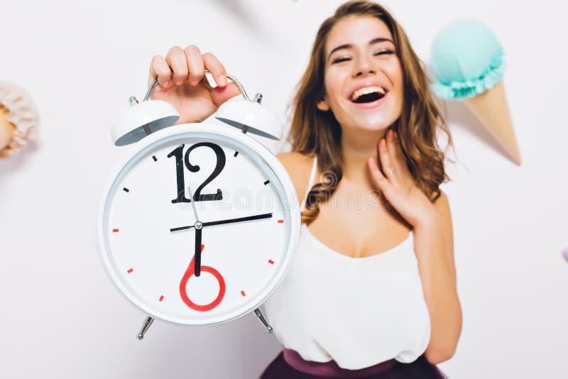 Возбужденная молодая женщина с большими часами в начале дня рождения руки ждать стоя на украшенной предпосылке : стоковое фото