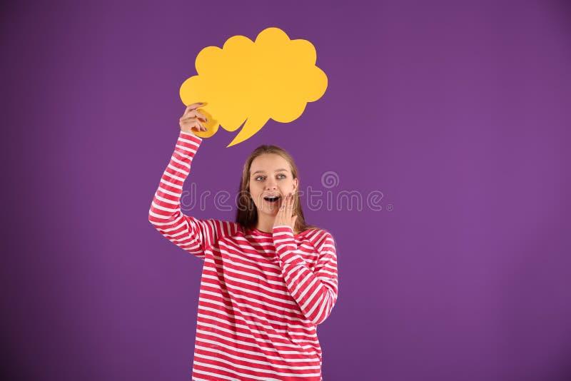 Возбужденная молодая женщина с пустым пузырем речи на предпосылке цвета стоковые фото